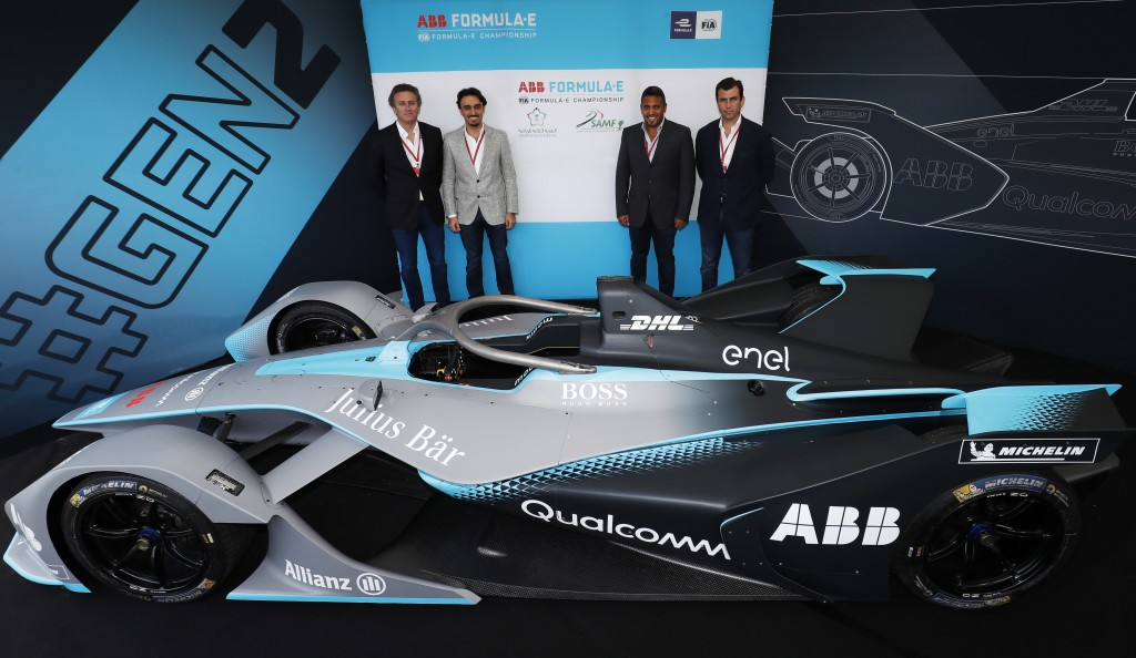 The_group_posing_alongside_the_next_generation_Formula_E_car